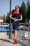 Piękna brunetki młoda kobieta w błękicie i czerwień ubieramy, będący ubranym czerwień heeled buty, okulary przeciwsłoneczni, chod Zdjęcia Royalty Free