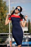 Piękna brunetki młoda kobieta w błękicie i czerwień ubieramy, będący ubranym czerwień heeled buty, okulary przeciwsłoneczni, chod Obraz Royalty Free