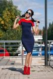 Piękna brunetki młoda kobieta w błękicie i czerwień ubieramy, będący ubranym czerwień heeled buty, okulary przeciwsłoneczni, chod Fotografia Royalty Free