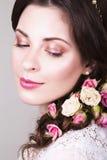 Piękna brunetki panna młoda ono uśmiecha się z naturalnym uzupełniał róże w jej fryzurze i kwitnie Obraz Stock