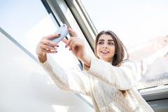 Piękna caucasian kobieta blisko okno, robić twarzy, uśmiechający się ranek i robić selfie, Fotografia Stock