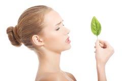 Piękna caucasian kobieta je świeżego zielonego liść. Fotografia Stock