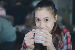 Piękna caucasian kobieta trzyma filiżankę kawy w jej ręce na zamazanym tle Fotografia Stock