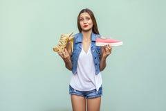 Piękna caucasian przypadkowa dziewczyna z piegami dostać wybierającą wygodnych sneakers lub szpilki niedogodną ale przystojną, Zdjęcia Stock