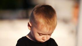 Piękna chłopiec bawić się z jego ręki i spojrzenia przy kamerą wtedy zdjęcie wideo