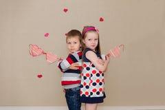 Piękna chłopiec i dziewczyna na tle serca Zdjęcia Stock