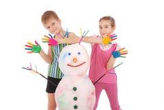 Piękna chłopiec i dziewczyna z rękami w farba koloru pobliskim bałwanie z barwionymi rogami i rękami Obrazy Stock