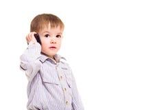 Piękna chłopiec opowiada na telefon komórkowy zdjęcia stock