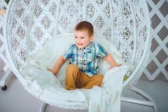Piękna chłopiec siedzi na huśtawce i pozach dla fotografa obrazy stock