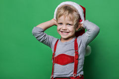 Piękna chłopiec ubierająca jak Święty Mikołaj pomagiera ono uśmiecha się Bożenarodzeniowy pojęcie Fotografia Stock