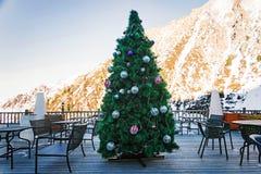 Piękna choinka dekorował z piłkami i girlandami na tle góry w plenerowej kawiarni w świetle dziennym h fotografia royalty free