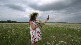 Piękna ciężarna dziewczyna robi selfie, fotografia z rumiankiem kwitnie outside zdjęcie wideo