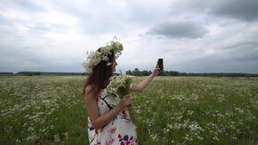 Piękna ciężarna dziewczyna robi selfie, fotografia z rumiankiem kwitnie outside zbiory