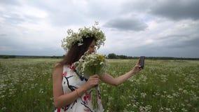 Piękna ciężarna dziewczyna robi selfie, fotografia z rumiankiem kwitnie outside zbiory wideo