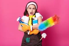 Piękna ciemna z włosami kobieta obejmuje udział butelki detergent, PP duster, ubierający w białej t koszula, brązu fartuch, hairb obraz stock