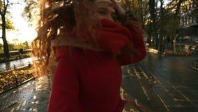 Piękna czerwieni głowy młoda kobieta joyfully biega w kolorowym jesień parku aleją, cieszy się jesieni ulistnienie, zwroty zbiory