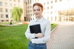 Piękna czerwona z włosami dziewczyna ściska notatniki z pracą domową i ono uśmiecha się szczęśliwymi z piegami fotografia royalty free