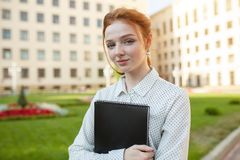 Piękna czerwona z włosami dziewczyna ściska notatniki z pracą domową i ono uśmiecha się szczęśliwymi z piegami obrazy royalty free