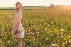 Piękna czuła słodka dziewczyna w białej koronki sukni z kosą na jego kierowniczy trwanie bosym w polu dandelions w słońcu zdjęcie royalty free