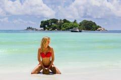 Piękna długa z włosami blondynki kobieta klęczy w czerwonym swimsuit, Seychelles Zdjęcia Royalty Free