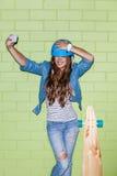 Piękna długowłosa dziewczyna z smartphone blisko zielonej cegły Obraz Stock