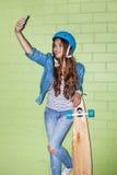 Piękna długowłosa dziewczyna z smartpnone blisko zielonej cegły Obrazy Royalty Free