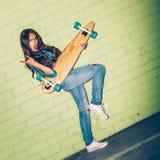 Piękna długowłosa kobieta z drewnianym longboard blisko zieleni Fotografia Stock