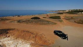 Piękna dama siedzi przy samochodowym kapiszonem przy seashore w Cypr zbiory