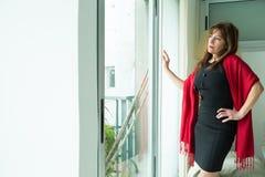 Piękna dojrzała kobieta patrzeje z okno zdjęcia stock