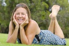 Piękna dojrzała kobieta relaksujący odpoczynek w parku Zdjęcia Stock