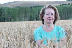 Piękna dojrzała kobieta z długim falistym włosy ubierał w comfy stylowej koszula pozuje w pszenicznym polu z spokojem Fotografia Stock