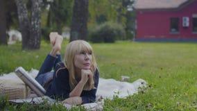 Piękna dorosła kobieta relaksuje na koc w parku zbiory wideo