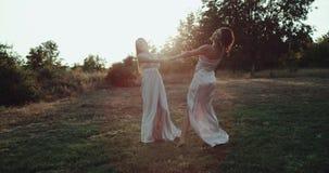 Piękna dwa dziewczyny po środku natury obracają wokoło i trzymający ręki szczęśliwe i uśmiechający się patrzeć each inny zdjęcie wideo