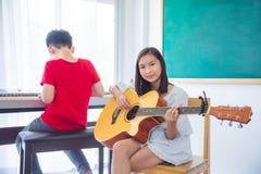 Piękna dziewczyna bawić się gitarę w sala lekcyjnej obrazy royalty free