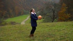 Piękna dziewczyna bawić się z piłką w jesień lesie jest szczęśliwa i uśmiechnięta Jest bardzo zabawą Jesień w zbiory wideo
