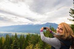 Piękna dziewczyna bierze fotografie w górach obraz royalty free