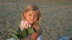 Piękna dziewczyna blondynka patrzeje w kamery obsiadaniu na seashore zbiory wideo