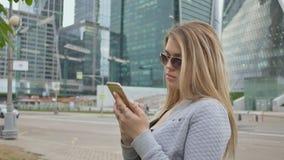 Piękna dziewczyna blondynka w okulary przeciwsłoneczni use telefon komórkowy przeciw tłu centrum miasta zbiory