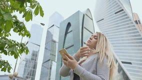Piękna dziewczyna blondynki use telefon komórkowy przeciw tłu centrum miasta zbiory wideo