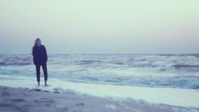 Piękna dziewczyna chodzi przy świtem na kipieli na mokrym piasku na brzeg, morzem Różowy niebo, fale, wiatr w zbiory