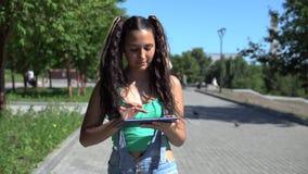 Piękna dziewczyna chodzi w parku używać pastylkę swobodny ruch zbiory
