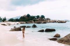 Piękna dziewczyna chodzi wzdłuż opustoszałej plaży wśród wielkich czerepów skały i greenery Ja dotyka z swój Obrazy Stock