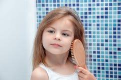 Piękna dziewczyna czesze jej włosy w łazience obrazy stock