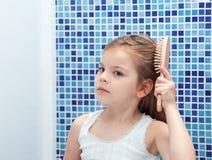 Piękna dziewczyna czesze jej włosy w łazience obraz stock