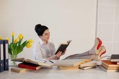Piękna dziewczyna czyta książki przy stołowym narządzaniem dla egzaminu zdjęcie royalty free