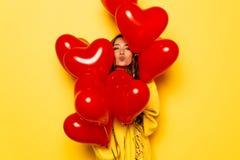 Piękna dziewczyna daje buziakowi patrzeje z serca kształtował lotniczych balony Zdjęcia Royalty Free