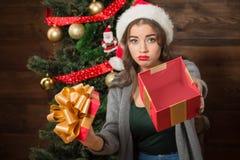 Piękna dziewczyna demonstruje pustego pudełko teraźniejszy pobliski nowego roku drzewo Zdjęcie Stock