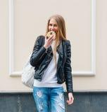 Piękna dziewczyna gryźć wyśmienicie pączka odprowadzenie na ulicach Europejski miasto Ciepła wiosna plenerowy Zdjęcia Stock