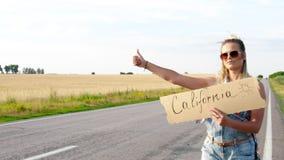 Piękna dziewczyna hitchhiking na drogi podróżować zbiory wideo