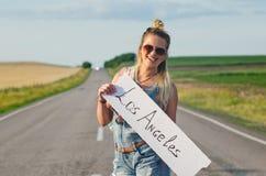 Piękna dziewczyna hitchhiking na drogi podróżować obraz royalty free